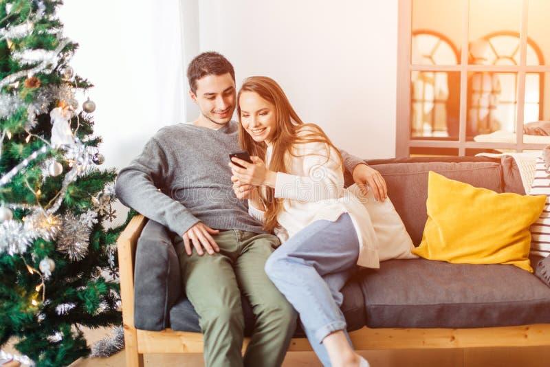 Молодые пары на Рожденственской ночи смотря сотовый телефон совместно стоковое изображение rf