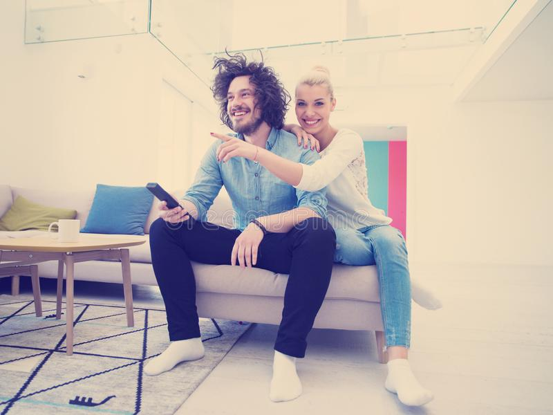 Молодые пары на софе смотря телевидение стоковые изображения