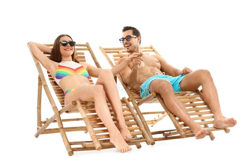 Молодые пары на шезлонгах против белой предпосылки стоковое фото