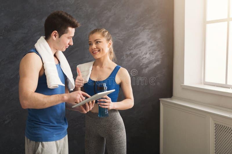 Молодые пары обсуждая план разминки на спортзале стоковое изображение rf