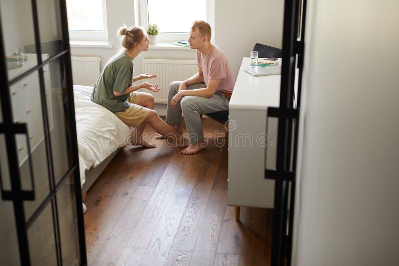 Молодые пары обсуждая проблему дома стоковые изображения
