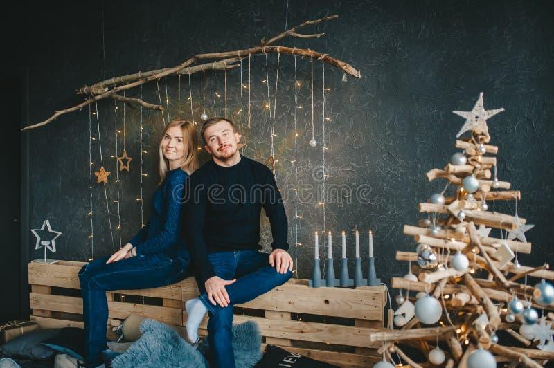 Молодые пары около ели рождества в комнате со стеной украшенной для рождества стоковая фотография rf