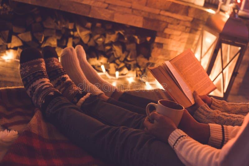Молодые пары около книги чтения зимы камина дома и выпивая какао стоковые фотографии rf