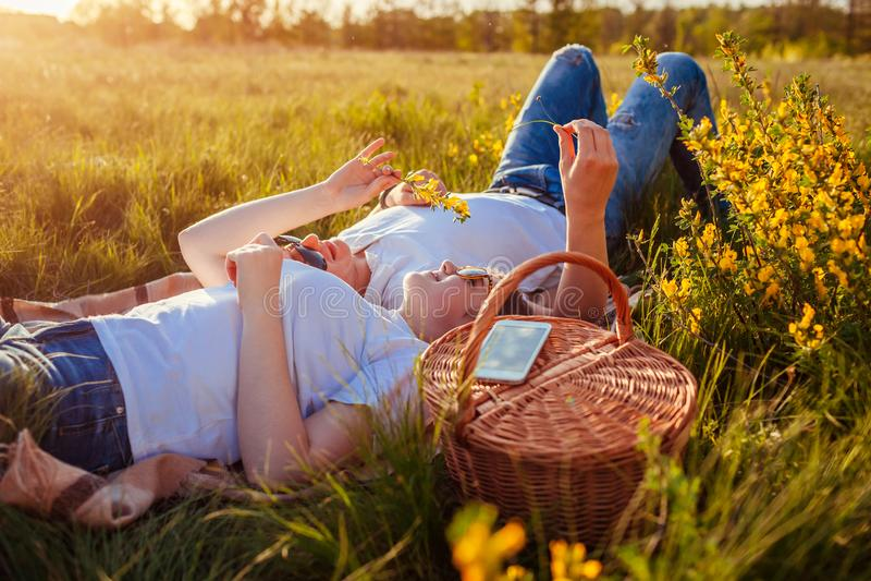 Молодые пары ослабляя позже имеющ пикник Женщина и человек лежа на траве и говоря на заходе солнца Парни охлаждая вне стоковые фотографии rf