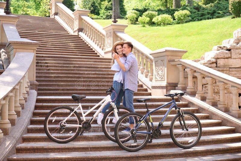 Молодые пары отдыхая после ехать велосипеды outdoors стоковые фотографии rf