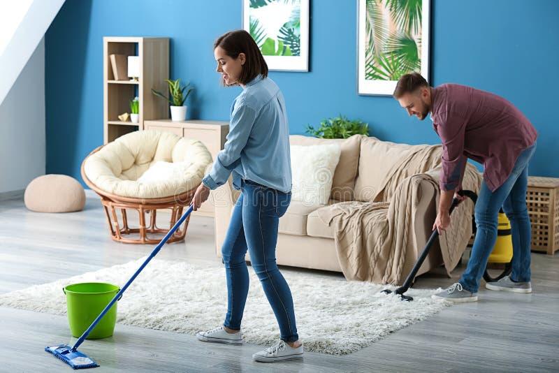Молодые пары очищая их квартиру совместно стоковое изображение rf