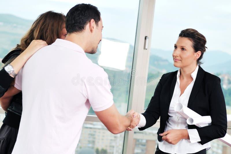Молодые пары покупая новый дом с агентом по продаже недвижимости стоковое фото rf