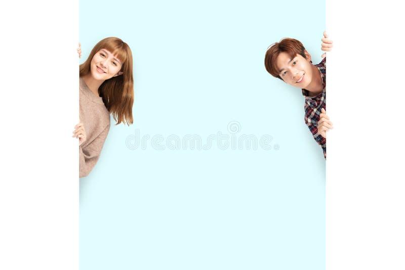Молодые пары представляя за пустой белой доской стоковые фото