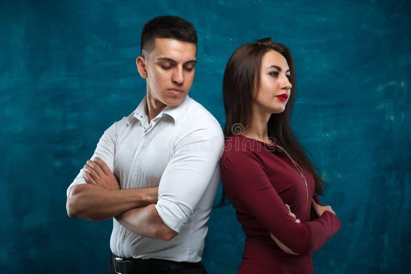 Молодые пары представляя на голубой предпосылке стоковое фото rf