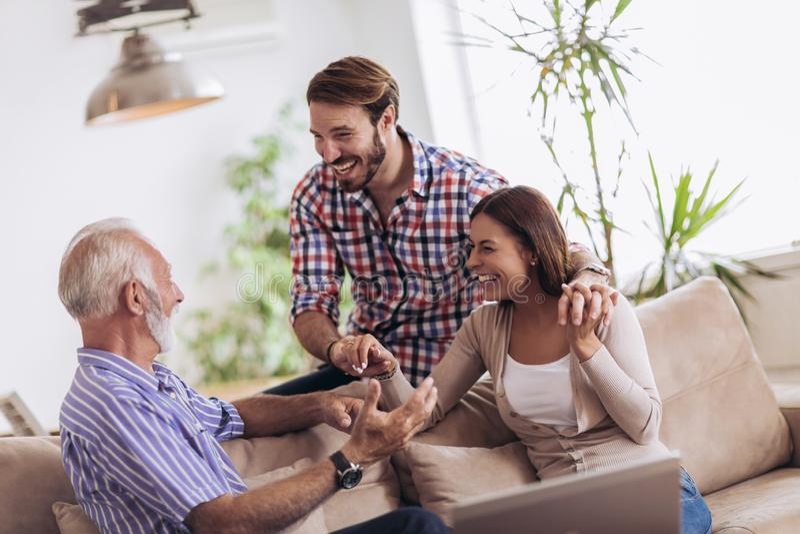 Молодые пары разговаривая с их старшим отцом стоковое изображение rf
