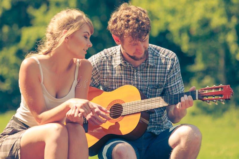 Молодые пары располагаясь лагерем играющ гитару внешнюю стоковые фото