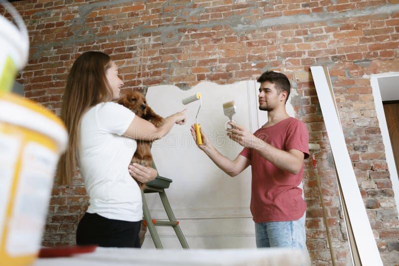 Молодые пары сами делая ремонт квартиры совместно стоковое изображение rf