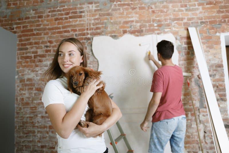 Молодые пары сами делая ремонт квартиры совместно стоковые изображения