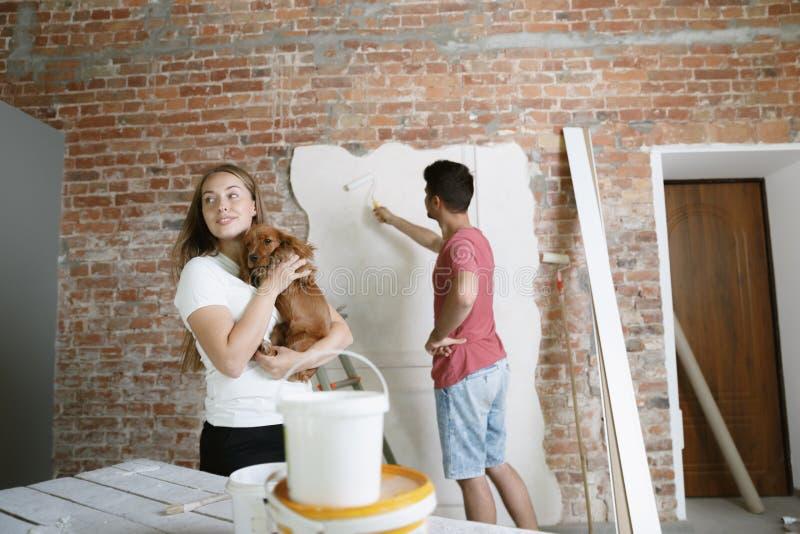 Молодые пары сами делая ремонт квартиры совместно стоковая фотография rf