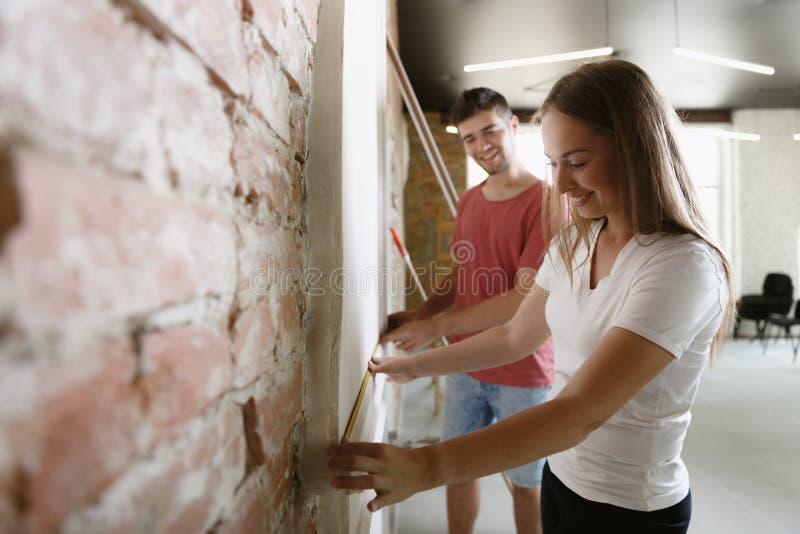 Молодые пары сами делая ремонт квартиры совместно стоковые изображения rf