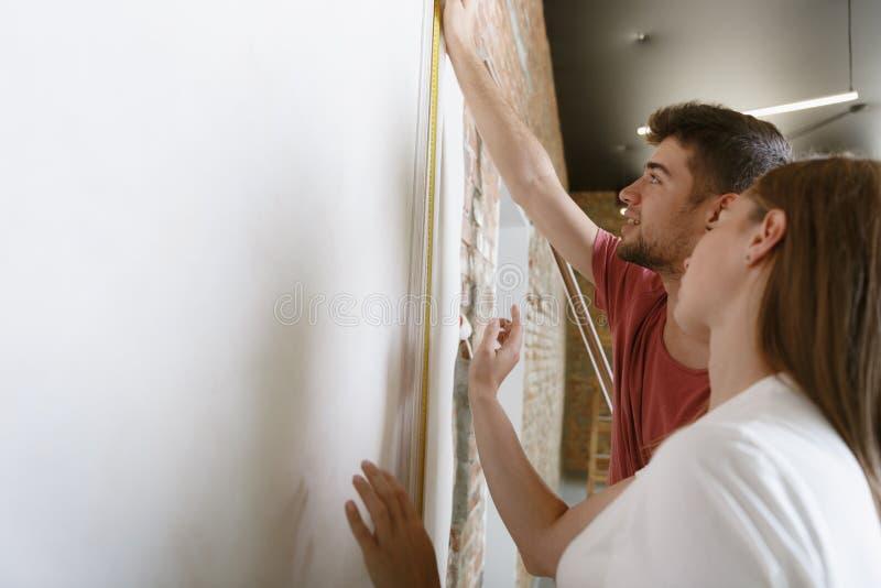 Молодые пары сами делая ремонт квартиры совместно стоковое изображение