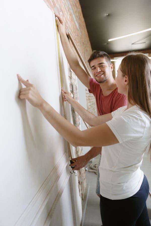 Молодые пары сами делая ремонт квартиры совместно стоковые фото