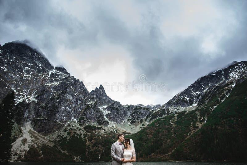 Молодые пары свадьбы представляя на береге озера Morskie Oko Польша, Tatra стоковое фото