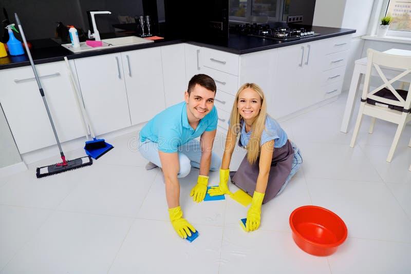 Молодые пары семьи делая чистку в кухне стоковые изображения