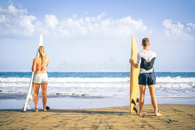 Молодые пары серферов стоя на пляже с surfboards подготавливая заниматься серфингом на высоких волнах - здоровых друзьях имея пот стоковое фото rf