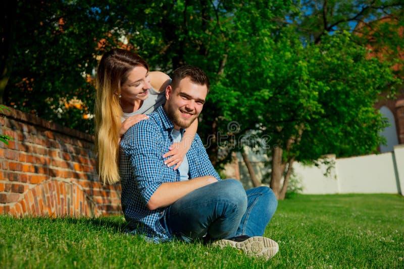 Молодые пары сидя на зеленой траве стоковое изображение rf