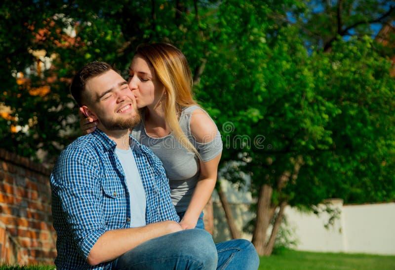 Молодые пары сидя на зеленой траве стоковые фотографии rf