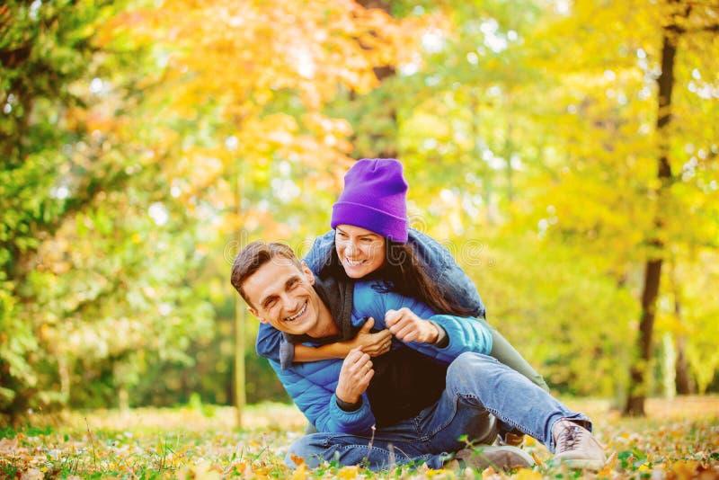 Молодые пары сидя на земле в парке времени сезона осени стоковые фотографии rf