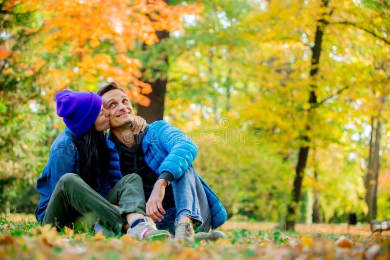 Молодые пары сидя на земле в парке времени сезона осени стоковое фото rf
