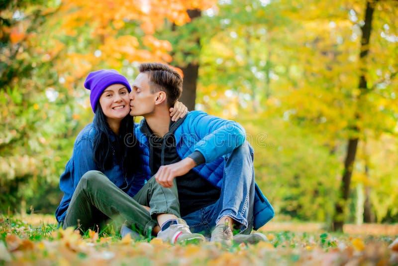 Молодые пары сидя на земле в парке времени сезона осени стоковая фотография rf