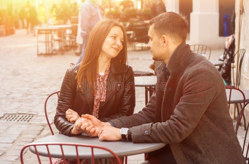 Молодые пары сидя на кафе улицы в пирофакеле солнца Романтичная дата стоковое фото rf
