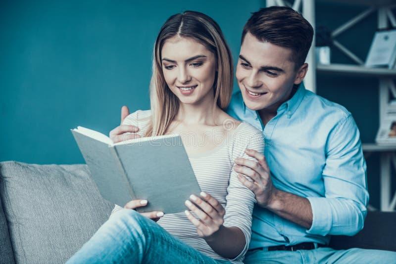 Молодые пары сидя на софе и книге чтения стоковая фотография