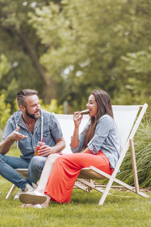 Молодые пары сидя на шезлонгах в зеленом саде стоковые фотографии rf
