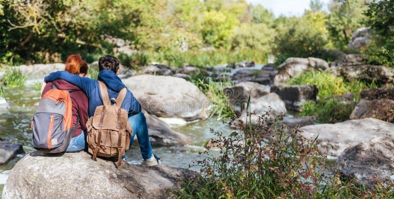 Молодые пары смотря естественный каньон с взглядом реки горы стоковая фотография