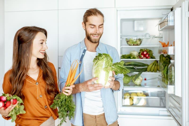 Молодые пары со здоровой едой на кухне стоковые изображения