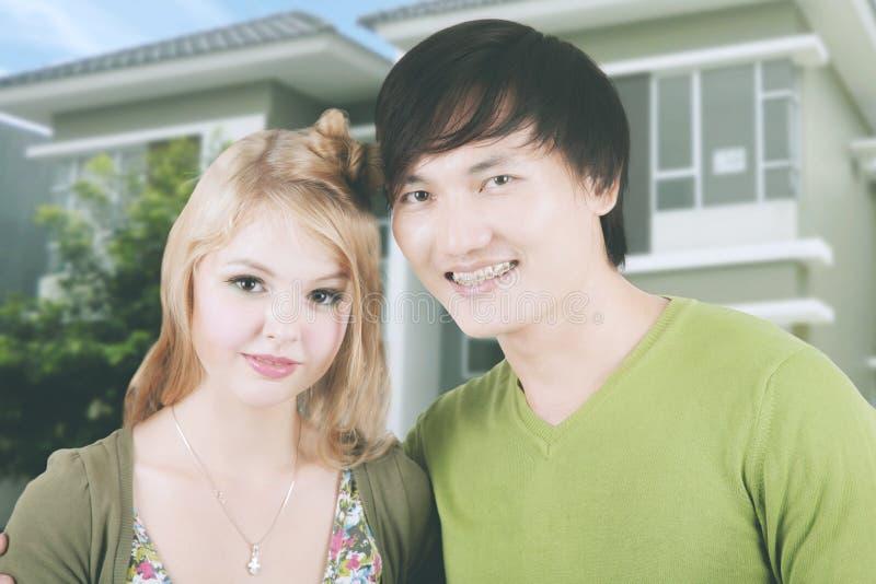 Молодые пары стоя около их нового дома стоковая фотография