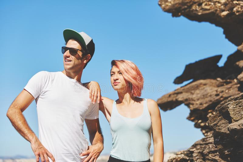 Молодые пары стоя совместно утесом смотря прочь стоковое фото