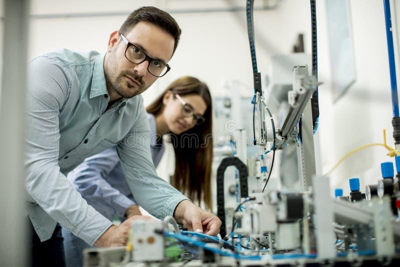 Молодые пары студентов на лаборатории робототехники стоковая фотография rf