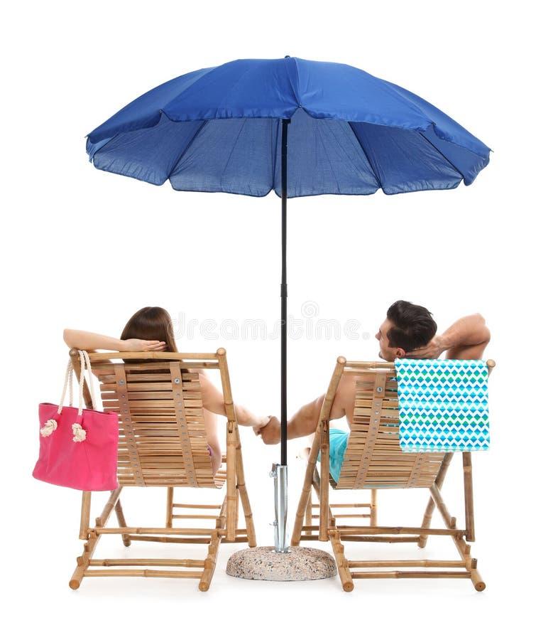 Молодые пары с аксессуарами пляжа на шезлонгах против белизны стоковое фото rf