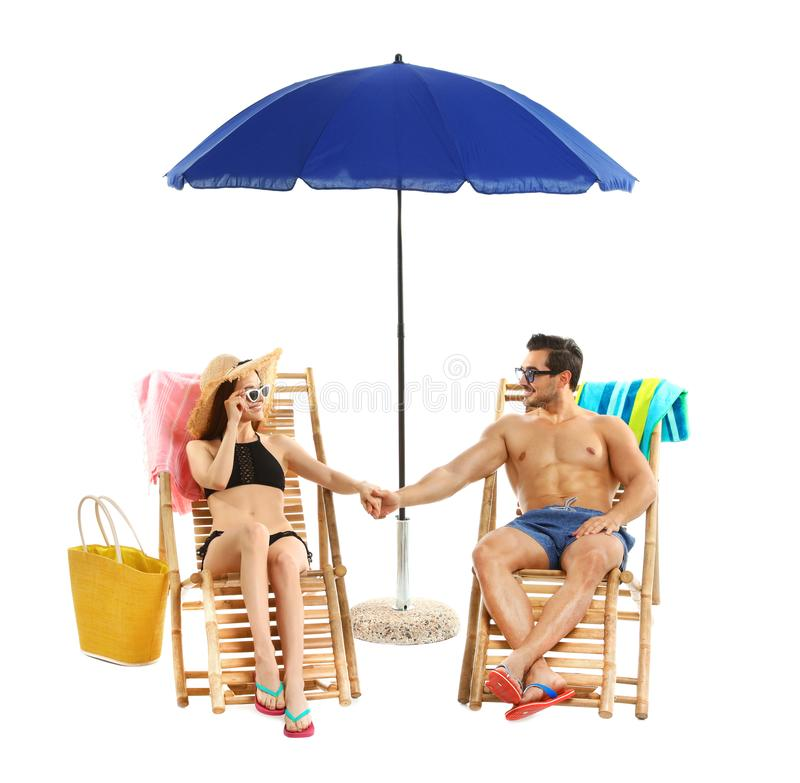 Молодые пары с аксессуарами пляжа на шезлонгах против стоковые изображения rf