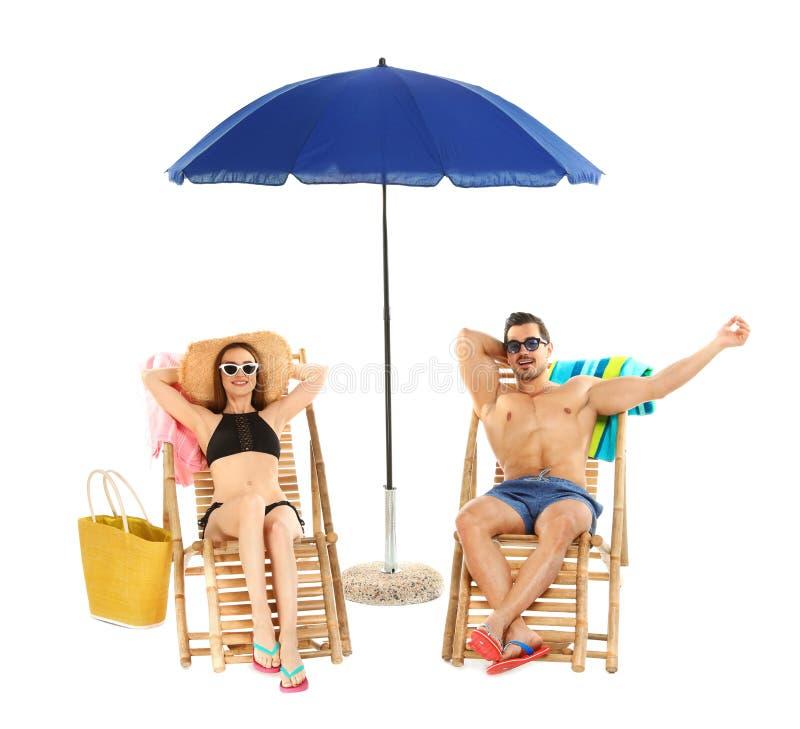 Молодые пары с пляжем на шезлонгах против белой предпосылки стоковые фотографии rf