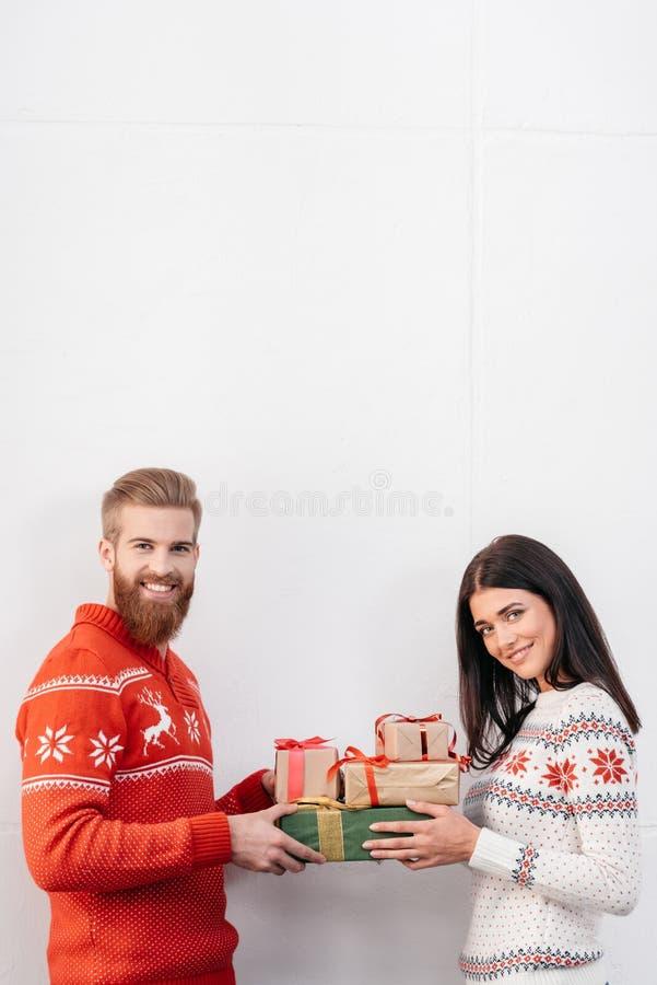Молодые пары с подарками на рождество стоковые изображения