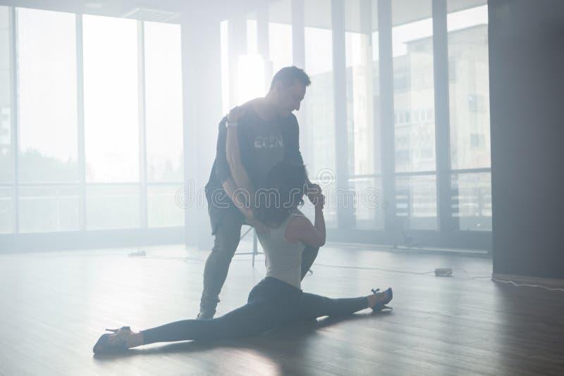Молодые пары танцоров практикуя снова и снова в их танцуя классе стоковое изображение