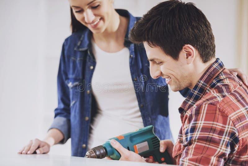 Молодые пары устанавливая мебель в новый дом стоковые фотографии rf