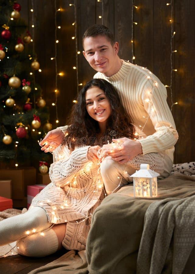 Молодые пары целуя в светах и украшении рождества, одетых в белизне, ель на темной деревянной предпосылке, романтичном вечере, w стоковая фотография rf