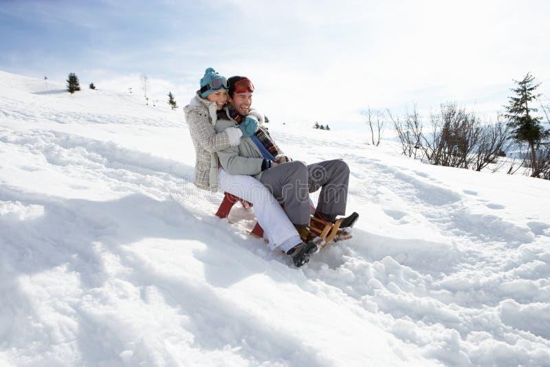 Молодые пары Sledding стоковое изображение