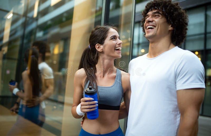 Молодые подходящие пары имеют тренировку в городской среде на солнечном дне стоковое фото rf