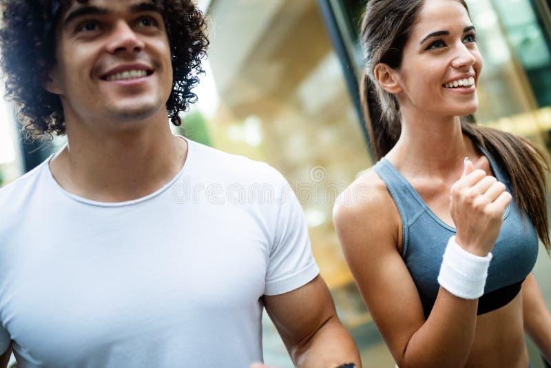 Молодые подходящие пары имеют тренировку в городской среде на солнечном дне стоковое изображение rf