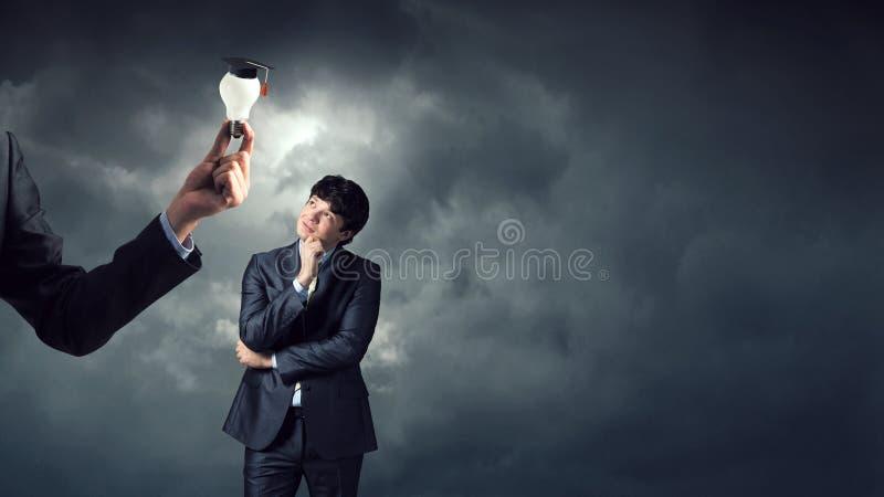 Молодые положение и мысль бизнесмена r стоковое фото rf