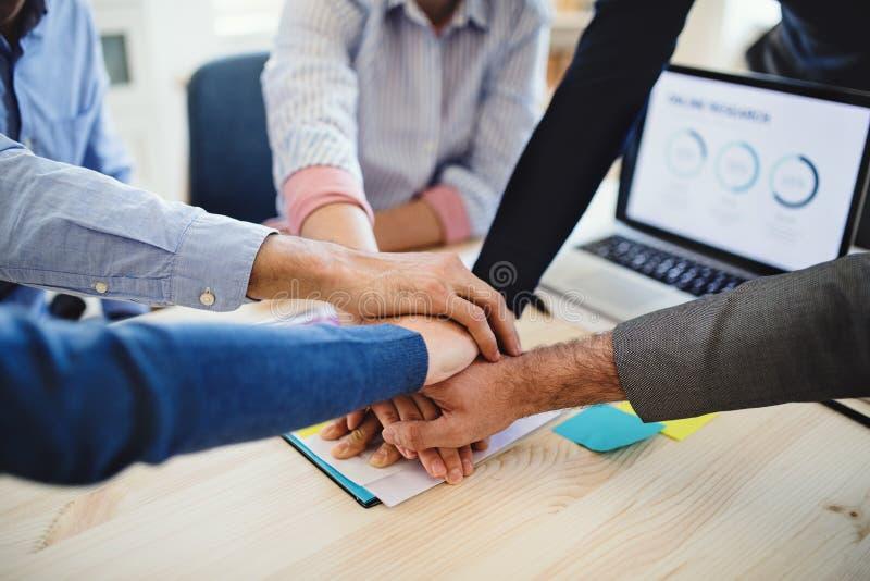 Молодые предприниматели сидя вокруг таблицы в современном офисе, кладя руки совместно стоковое изображение rf