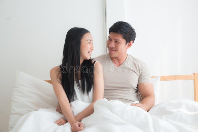 Молодые прекрасные пары на кровати вместе с усмехаться и счастьем стоковые фотографии rf